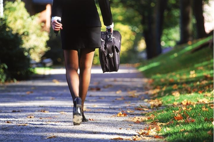 Businesswoman with black suit and briefcase walking on pathway to work