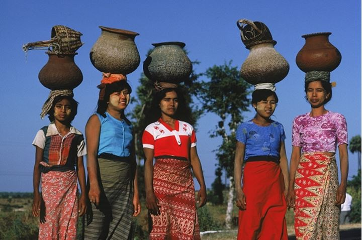 Women with sun block creme on their faces carrying clay pots filled with water in Myanmar