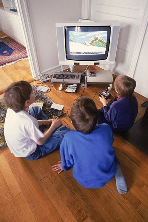 Three boys on floor using home television to play video games