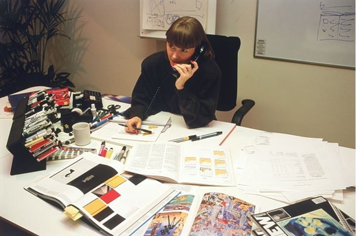 Art director in small ad agency or publishing house working at desk and talking on telephone in Sweden