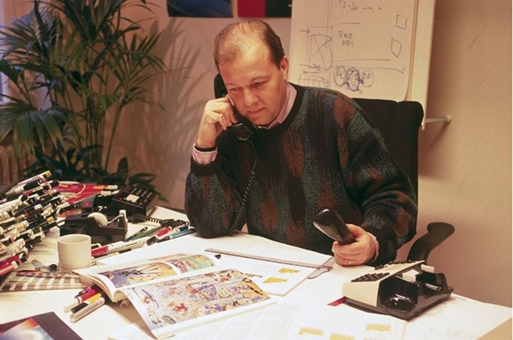 Art director with ad agency or publishing house at desk talking on two telephones.