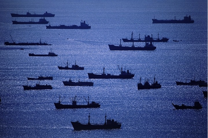 Silhouetted cargo ships anchored outside Singapore harbor at dawn