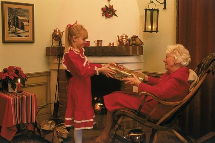 Grandaughter sharing Christmas presents with Grandmother at home near fireplace in Sweden