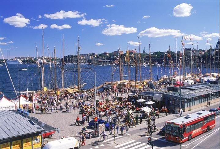 Busy waterfront with ships and restaurants along Skeppsbron during Stockholm summer
