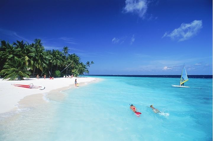 Couple snorkling in aqua waters with windsurfer at Fihalhohi Island in Maldives
