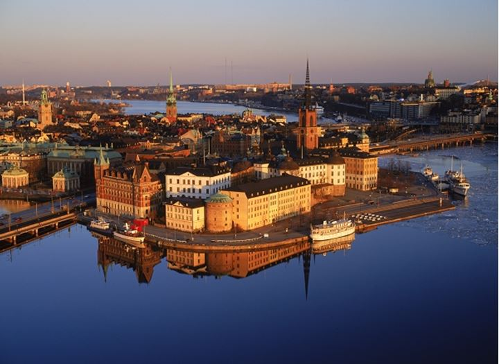 Overview of Riddarholmen Island with anchored boats reflecting off glassy Riddarfjarden waters in Stockholm at sunset