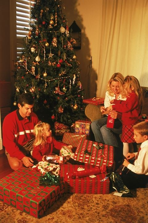 Family of five around Christmas tree at home exchanging presents