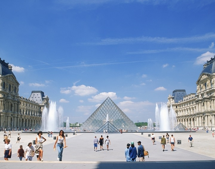 Pyramide fountains and tourists at Louvre Museum in Paris