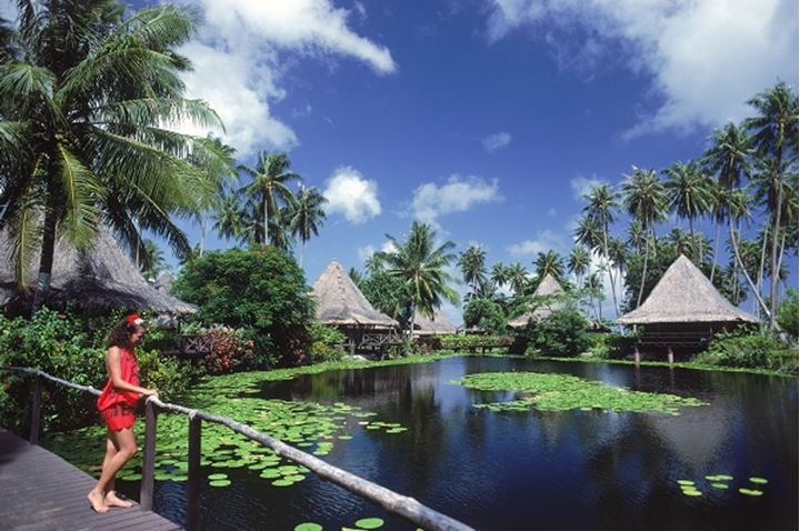 Woman in red sarong at Hotel Bali Hai on Huahine Island in French Polynesia