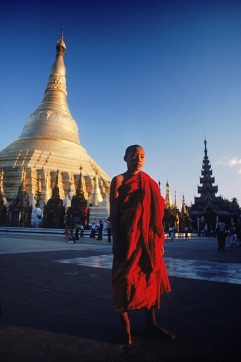 The Golden Spire of the Shwedagon Pagoda and young Buddhist in sunset light at Rangoon, Myanmar