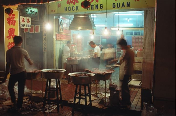China Town in Singapore with men roasting and frying pork slabs at night
