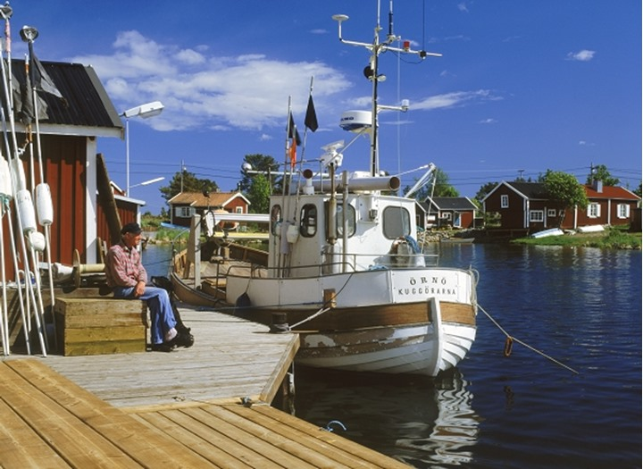 Fisherman and his fishing boat at Baltic Sea island village of Kuggoren on Swedens East Coast