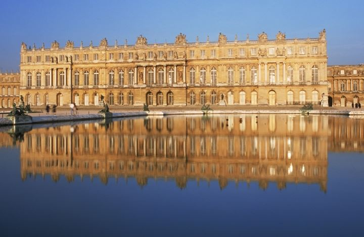Palace of Versailles near Paris reflecting off pond at sunset