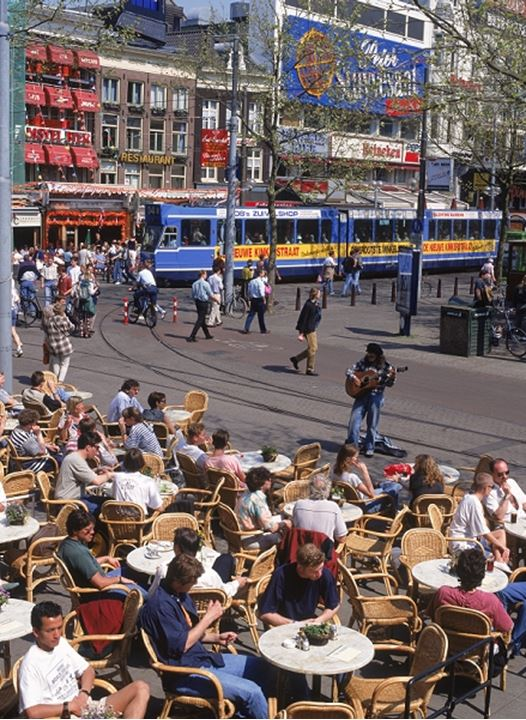 Trams and people in outdoor cafes on Rembrandt Platz in Amsterdam in summer