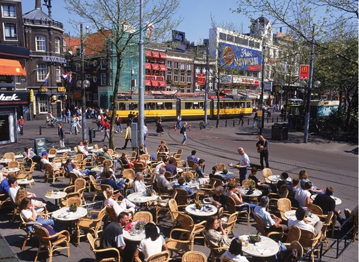 Trams and people in outdoor cafes on Rembrandt Platz in Amsterdam