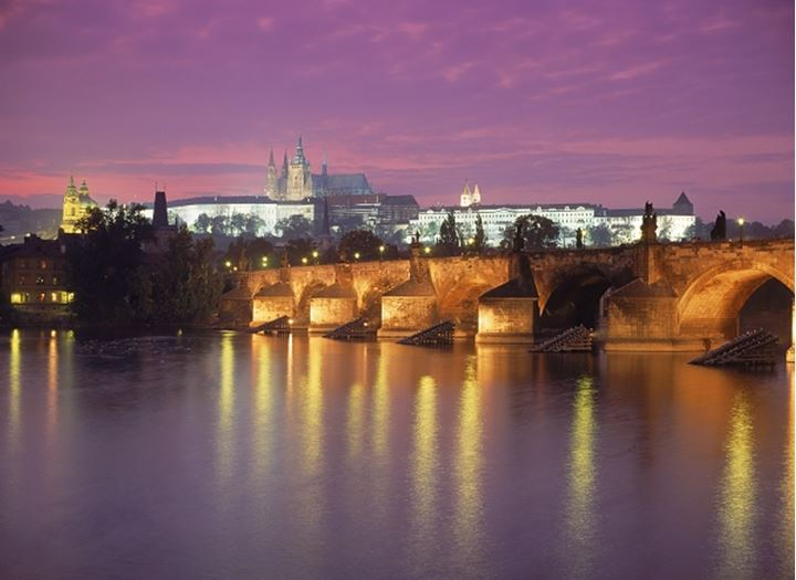 Charles Bridge across the Vltava River illuminated at night with Hradcany Castle and St. Vitus Cathedral