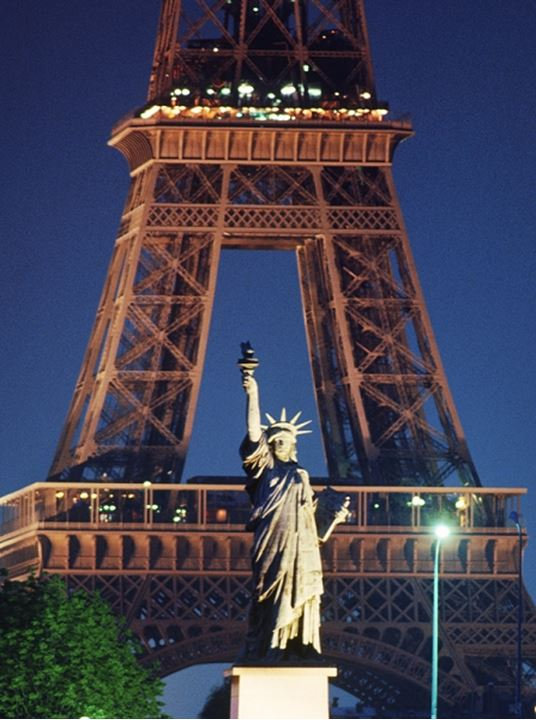 Statue of Liberty and Eiffel Tower above River Seine at night in Paris France