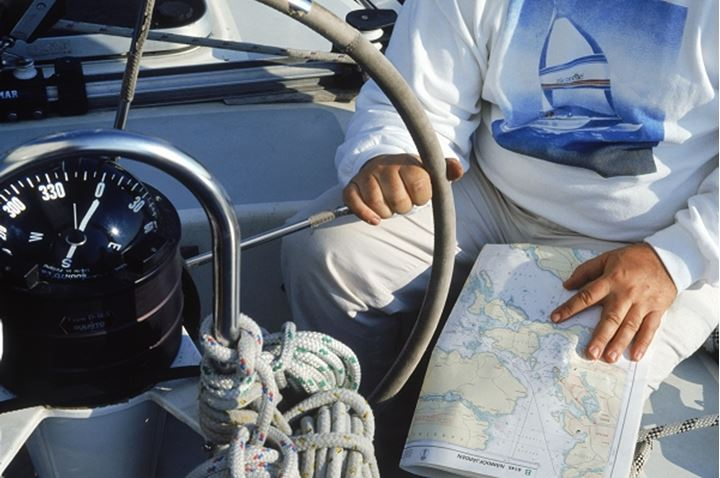 Man at helm of sailboat with compass and charts