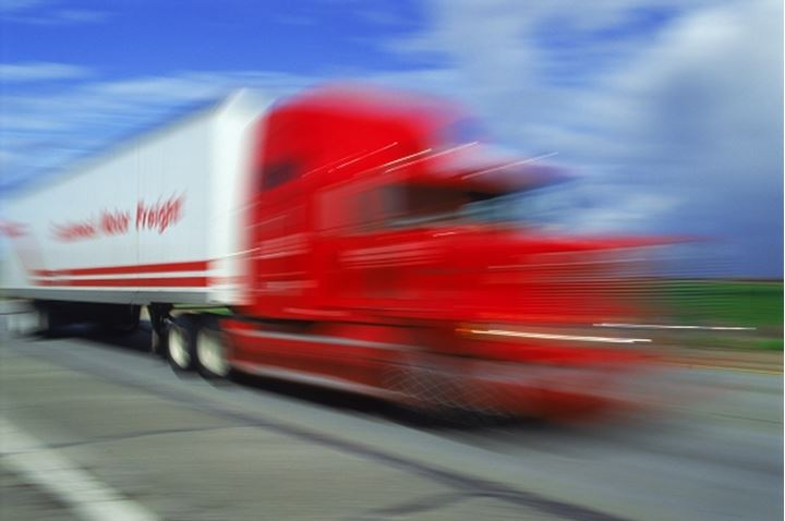Red truck cab and trailer speeding along California highway