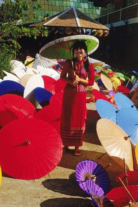 Thai woman surrounded by painted umbrellas in Chiang Mai Thailand