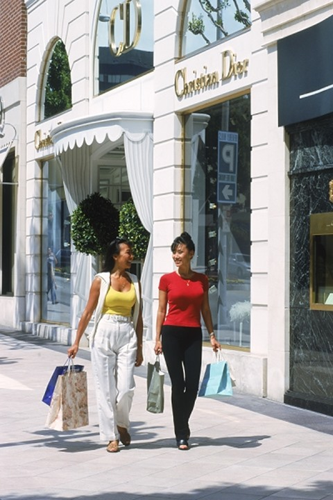 Two Asian women with shopping bags on Rodeo Drive in Beverly Hills