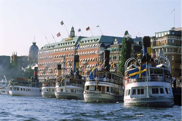Passengers and steamships on Archipelago Boat Day in Stockholm with Grand Hotel