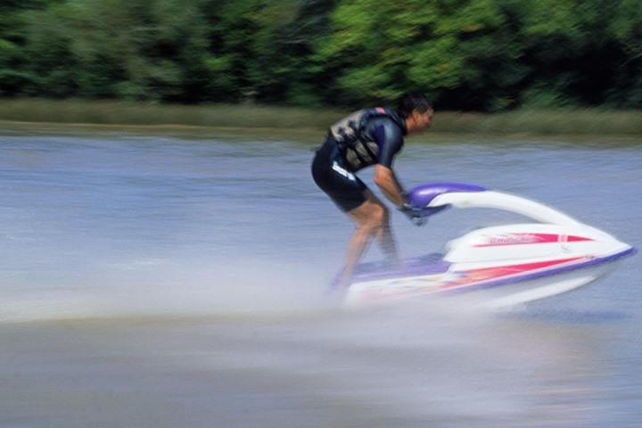 Man wearing life jacket and wetsuit racing jet ski on river