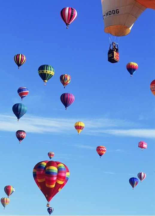 Floating balls of colorful silk carrying baskets of people through clear blue skies