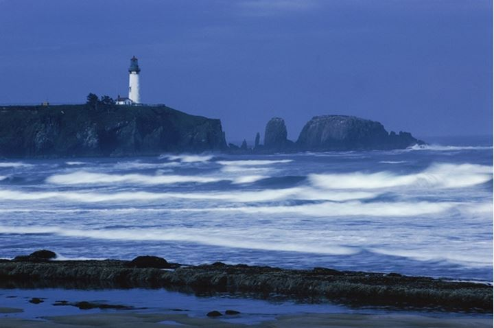 Yaquina Head Lighthouse on headlands at Newport, Oregon over Pacific Ocean