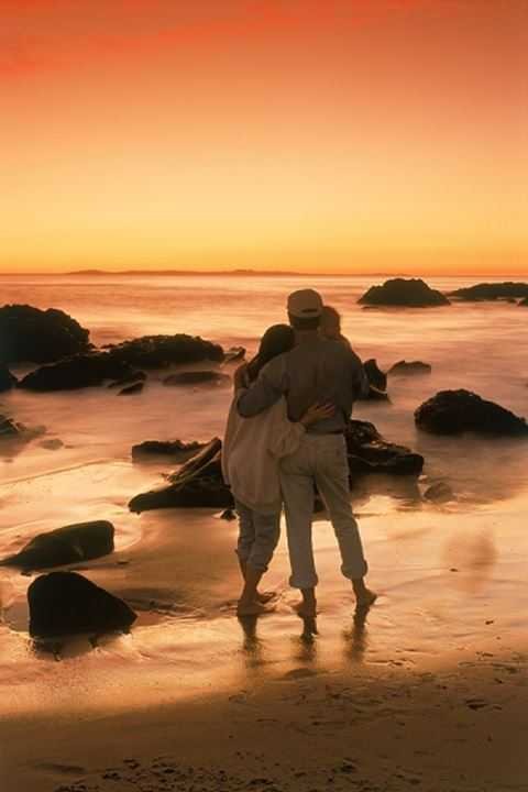 Couple barefoot on sandy shore at sunset in Laguna Beach, California