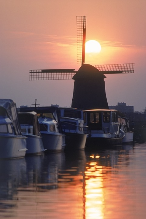 Boats moored along canal near Alkmaar with sun setting behind windmill in Holland