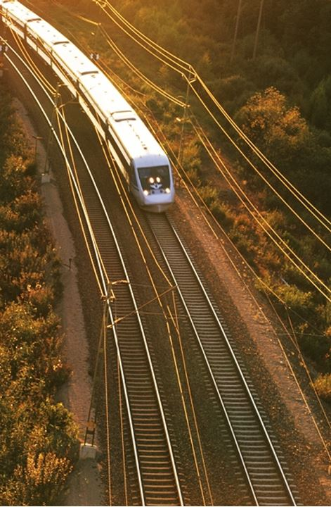 Speed train racing down tracks across Swdish countryside lined by power lines