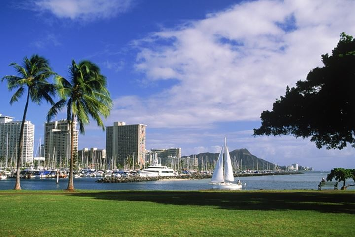 Sailboat entering Ala Wai Harbor with Diamond Head and Waikiki Hotels from Magic Island