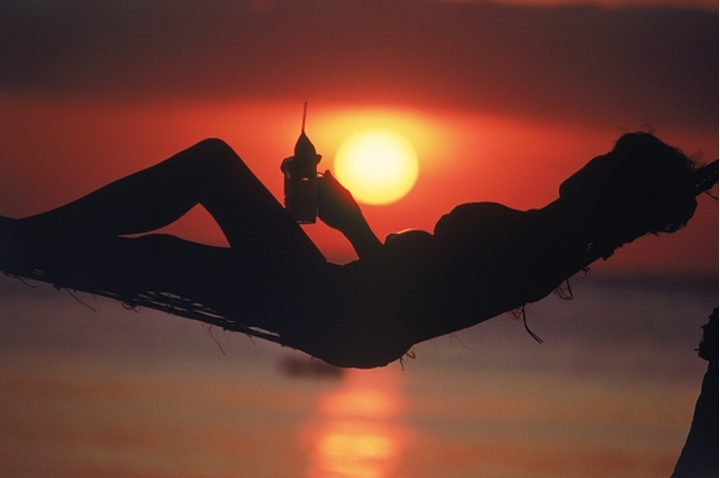 Woman in hammock with drink in hand silhouetted at sunset