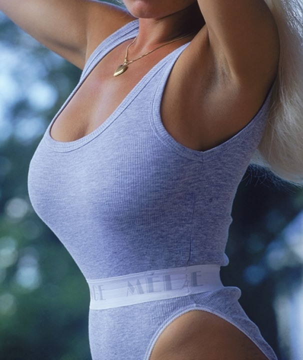 Buxom blond woman wearing grey gym suit