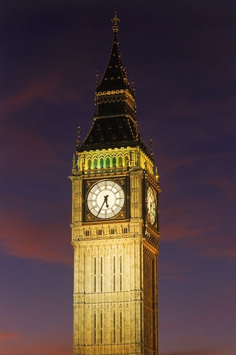 Big Ben standing above Westminster Bridge and River Thames in London at night