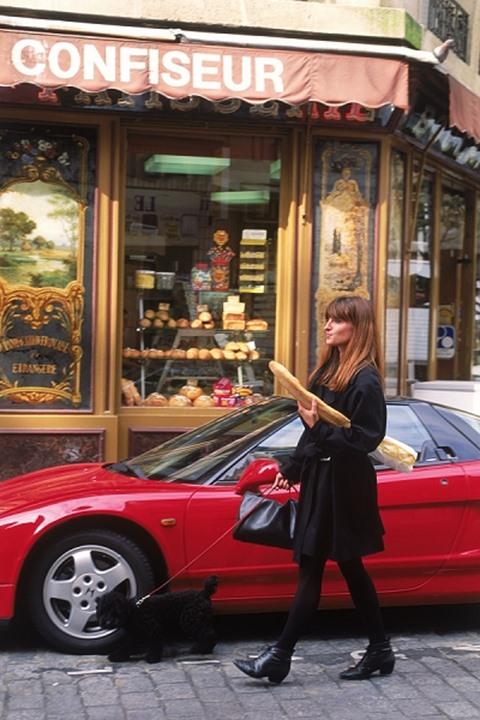 Woman in Paris leaving boulangerie with baguette passing red sports car with French poodle on cobblestone street