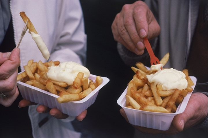 Couple eating French fries or pommes frites with mayonnaise in Belgium