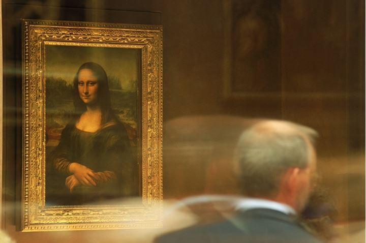 Visitors looking at painting of Mona Lisa by Leonardo da Vinci in Grand Gallery of the Louvre Museum