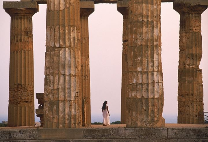 Woman walking through ruins of Greek temple from 7th Century BC at Selinunte in Trapani Province on Sicily