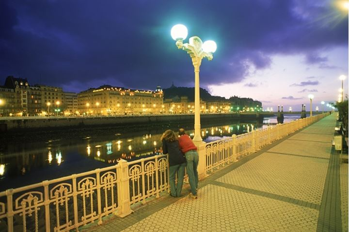 Couple under street lamp on Paseo de Francia along Urumea River in San Sebastian at night