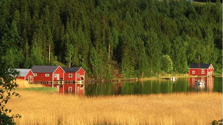 Red country houses along inland waterways on the High Coast of Angermanland in Sweden