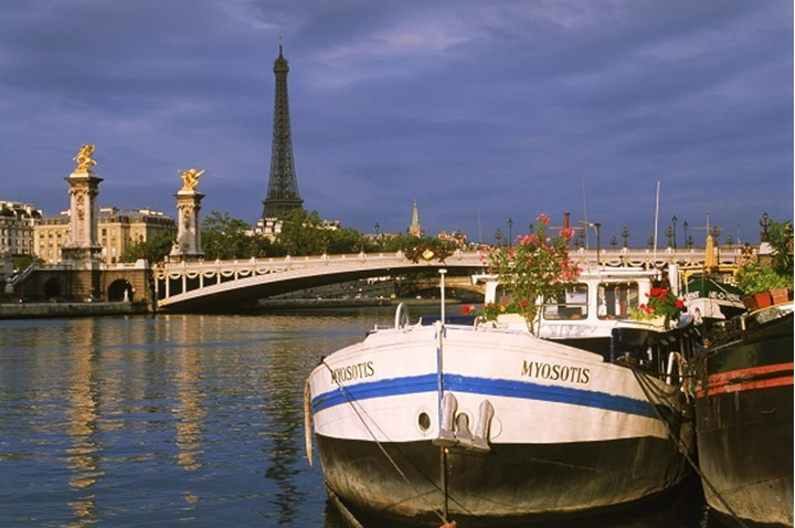 Houseboats moored along banks of  River Seine near Eiffel Tower