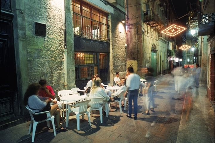 Outdoor cafes and restaurants at night on walking streets of Alicante, Spain