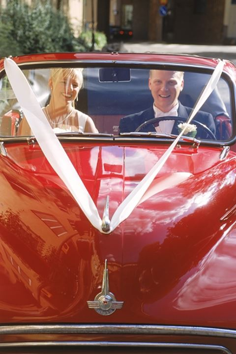 Couple on wedding day in bright red classic car