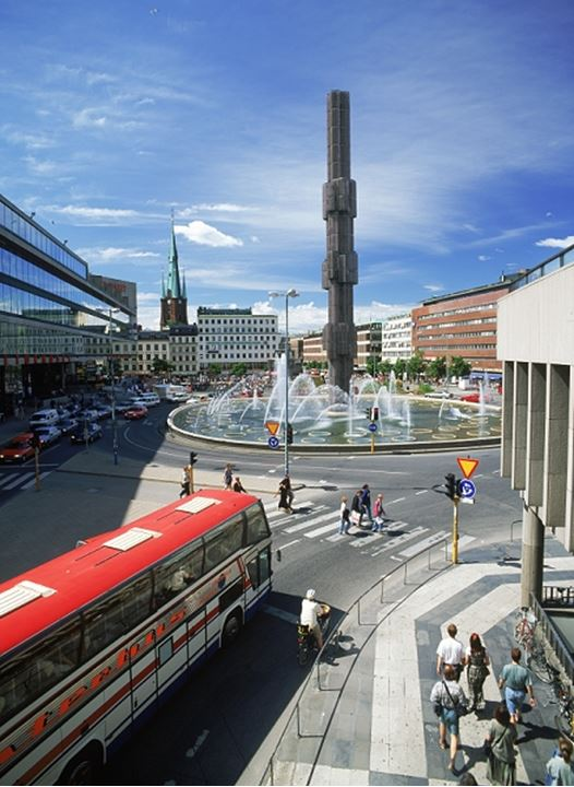 Foot traffic and bus with the glass obelisk and fountain at Sergelstorg roundabout in Stockholm