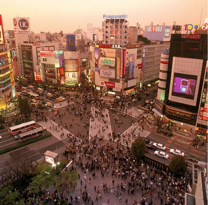 Overview of Shibuya district with pedistrian traffic and neon signs at dusk in Tokyo