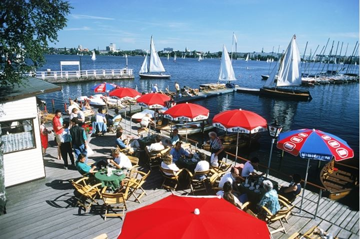 Pier cafe and tables with sailboats on Alster Lake in the middle of Hamburg in Northern Germany