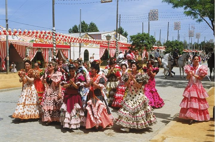 """Women with traditional colorful dresses during """"Feria De Sevilla"""" festival in Seville, Spain"""