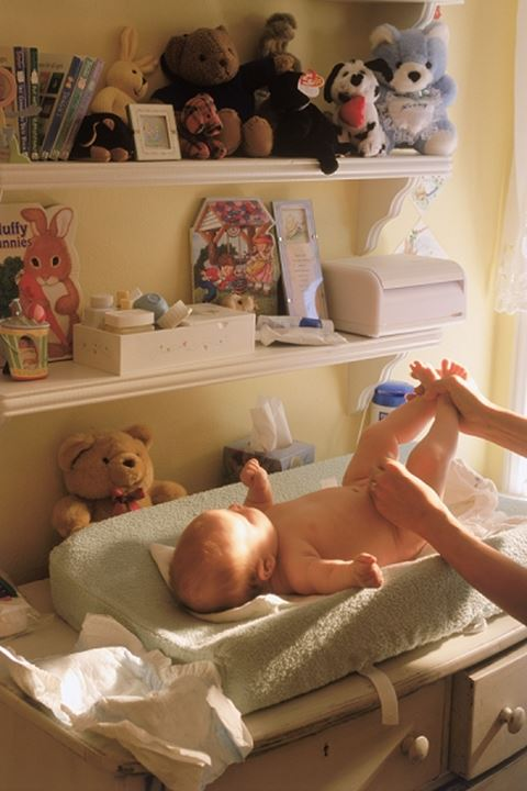 Mother changing babies diaper at home under shelves of baby toys